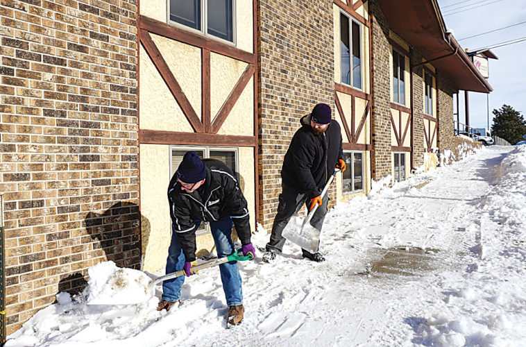 Jill Schramm/MDN Shovel wielders move snow away from a building at 328 2nd Avenue SW on Jan. 17 to guard against water leaking into the structure during thawing weather.