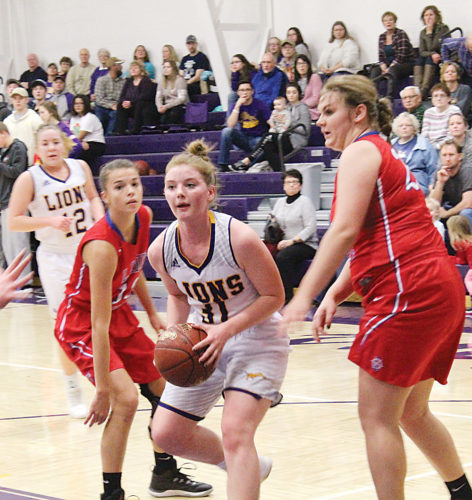 Mark Jones/MDN Bishop Ryan's McKinlee Harmon splits the defense of two Des Lacs-Burlington defenders during the first period of their Class B District 12 contest Friday night at Bishop Ryan.