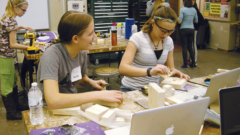 Andrea Johnson/MDN Eighth-graders Danielle Aberle, left, and Justice Nerad work on making candy dispensers during the MakeHERspace event at Minot High School-Central Campus on Saturday.