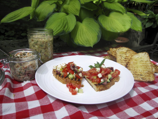 This Sunday, May 22, 2016 photo, shows salmon salad in a jar, left, next to the white bean salad and chopped greek salad on grilled bread in New York. This recipe spells out three different toppings, all vaguely Mediterranean: a white bean salad with fresh fennel thickened with mashed beans so that the filling sticks to the bread; smoked salmon rillettes, finely-chopped salmon flavored with capers, lemon and fresh herbs and bound with sour cream; and a chopped Greek salad. (AP Photo/Sara Moulton)