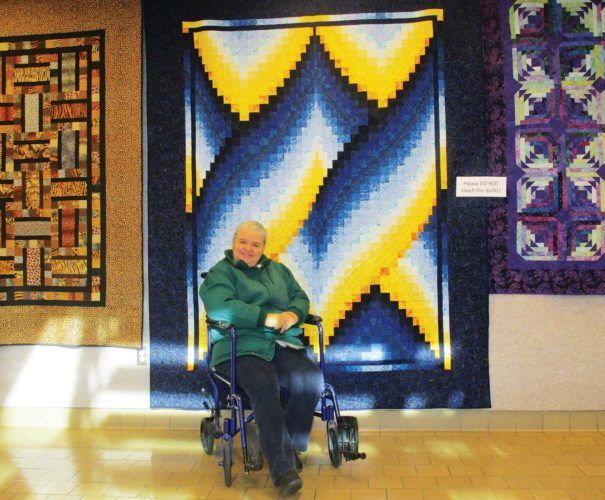 Allan Blanks/MDN Jan Clark, a member of the Minot Prairie Quilt Guild welcomes everyone to explore the works of Minot area  quilters.