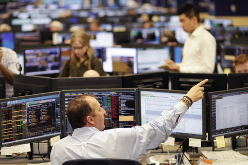 In this Jan. 12, 2017 photo, traders work on the Mizuho Americas trading floor in New York. Stocks around the world continued to push higher Monday, Feb. 13, 2017, and U.S. indexes again hit records as bond yields limbed. (AP Photo/Mark Lennihan)