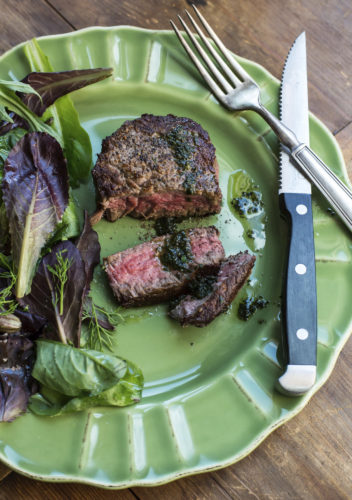 This October 2016 photo shows filet mignon with basil pistou in New York. This dish is from a recipe by Katie Workman. (Sarah E Crowder via AP)