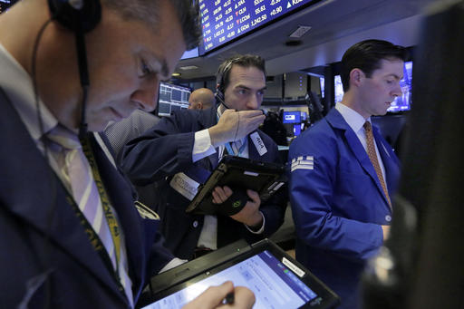 Trader Gregory Rowe, center, works on the floor of the New York Stock Exchange, Friday, Feb. 17, 2017. Stocks are posting moderate declines in early trading as a fast-paced market rally of the past two weeks goes into reverse. (AP Photo/Richard Drew)