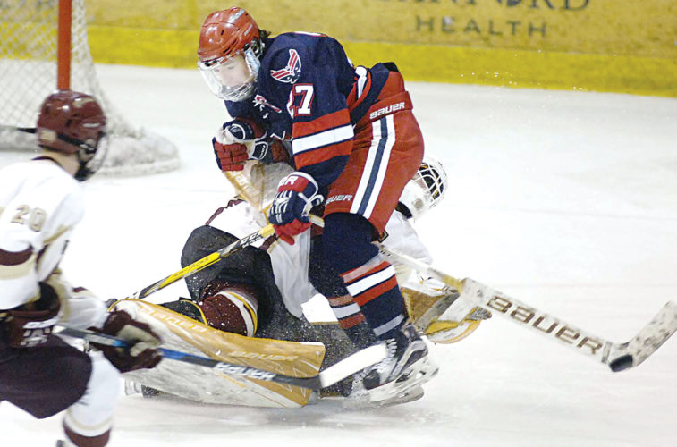 Submitted Photo Bismarck Century's Isaiah Thomas, front, and Minot goaltender Odin Nelson collide away from the net while going for the puck during the West Region tournament semifinals at the VFW Sports Center in Bismarck on Friday. Minot High won 4-3 in triple overtime to advance to the championship match. Photo courtesy of Bismarck Tribune.