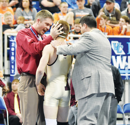 Garrick Hodge/MDN  Minot High coach Justin Racine, left, celebrates with wrestler Brody Armstrong, center, after Armstrong won the Class A 126-pound state title Saturday at the Fargodome.