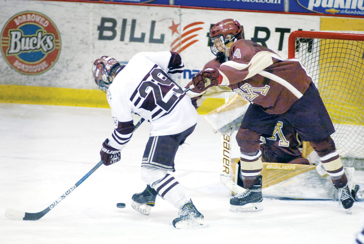 Submitted Photo Bismarck's T.J. Irey (29) gathers in the puck in front of the Minot net before resetting and shooting the puck past Patrick Heide and goaltender Odin Nelson as part of his hat trick, all in the second period, of the West Region hockey tournament championship game at the VFW Sports Center on Saturday.  Photo courtesy Mike McCleary, Bismarck Tribune.