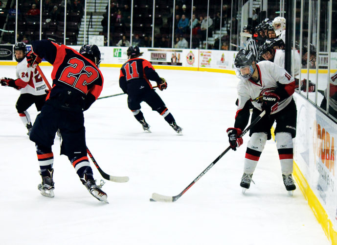 Alex Eisen/MDN  Minot State's Jeremy Johnson (11) steals the puck away from a Midland skater Saturday evening at Maysa Arena. The No. 1 Beavers won 4-2 on Senior Night.