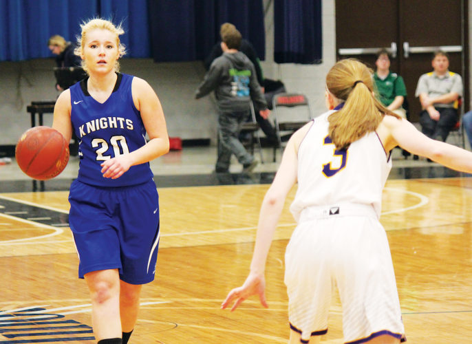 Alex Eisen/MDN  Our Redeemer's Morgan Olson (20) dribbles the ball in the District 12 championship game against Bishop Ryan on Feb. 11. Both teams advanced to the Region 6 tournament starting today at the Minot Auditorium.