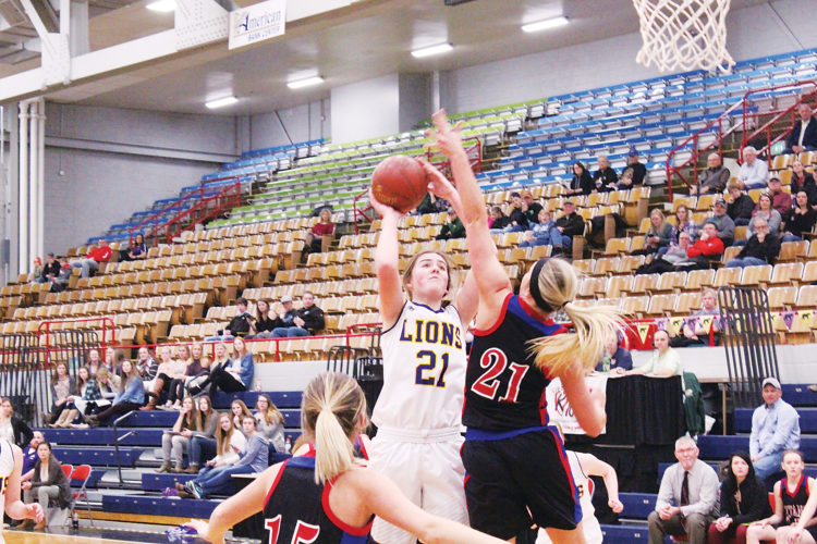 Cutline: Mark Jones/MDN Bishop Ryan's Annika Stewart goes up for a shot as Towner-Granville-Upham's Angie Anderson goes up for a block during the first period of their Class B Region tournament contest Monday at the Minot Municipal Auditorium. Ryan won 53-18.