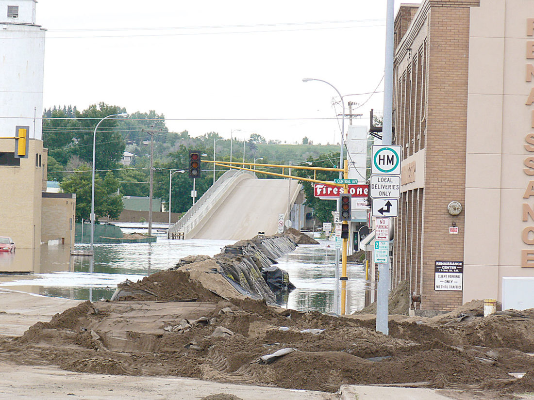 File photo  Water runs over Third Street downtown as flooding began in June 2011. Work on an enhanced flood protection project in Minot is scheduled to begin later this year.