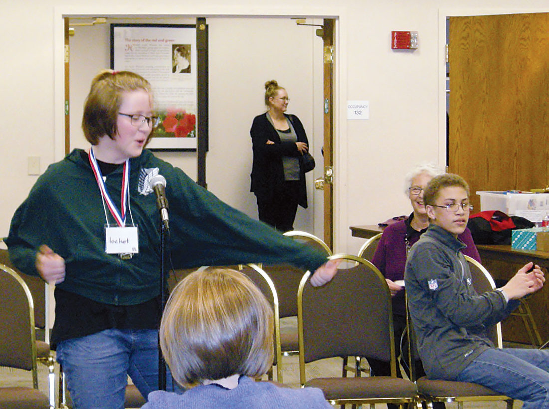 Andrea Johnson/MDN Erik Ramstad Middle School eighth-grader Chloe Carlson reacts as she wins the Ward County Spelling Bee on Wednesday at Minot State University as runner-up Christopher Jenner watches in the background. Deb Sisco, ELL coordinator for the Minot Public Schools and a helper at the spelling bee, is pictured in the back.