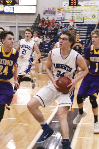 Mark Jones/MDN Our Redeemer's Christian School's Leyton Lang powers his way to the basket during the second half of a Class B District 12 tournament semifinal contest against Lewis & Clark-Berthold Saturday night at the Minot Municipal Auditorium. The Knights won at the buzzer 61-60.