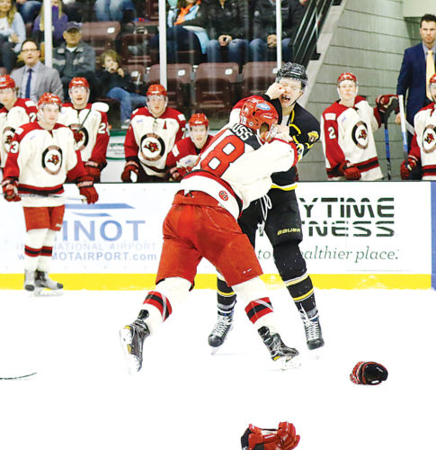 Photo courtesy of Steve Silseth Minot Minotauros forward Austin Koss (18, white and red), lands a right hook on Austin Bruins forward Michael Piehler (18, yellow and black) during a fight at a NAHL hockey game Saturday at Maysa Arena. The Tauros beat Austin 3-2.