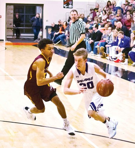 Photo courtesy of Matthew Semisch/Bottineau Courant Bottineau guard Max Henry tries to get around Westhope-Newburg defender AJ Jiles during the teams' District 11 semifinal Saturday in Rugby. W-N defeated Bottineau 71-70.