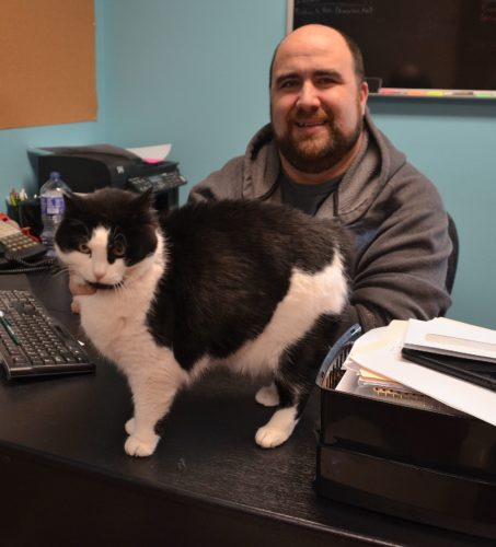 Eloise Ogden/MDN Randy McDonald, Souris Valley Animal Shelter director, with Bedelia, the shelter's friendly cat, said making sure a pet and the pet's breed are right for your home is an important part when adopting a new pet.
