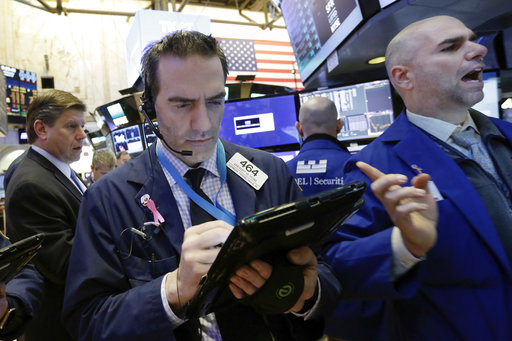 Trader Gregory Rowe, center, and specialist Philip Finale, right, work on the floor of the New York Stock Exchange, Wednesday, March 22, 2017. Stocks are treading water in early trading as gains in high-dividend stocks are outweighed by drops in banks and other sectors. (AP Photo/Richard Drew)