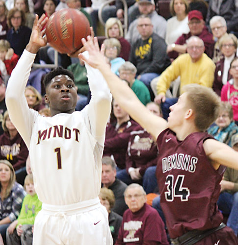 Alex Eisen/MDN Magi senior KyJuan Johnson (1) rises up and knocks down a 3-pointer in the first half of a West Region game against Bismarck High earlier this season.