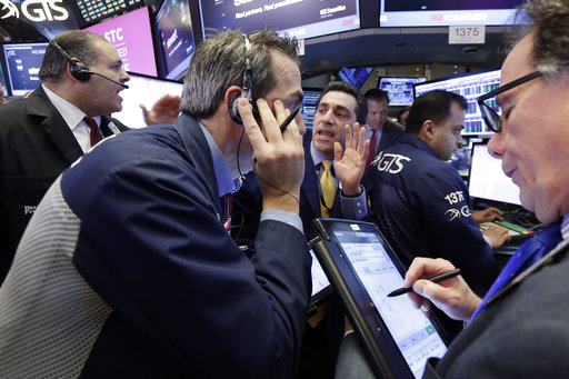 Specialist Peter Mazza, center, works with traders on the floor of the New York Stock Exchange, Wednesday, March 29, 2017. Stocks are opening mostly lower on Wall Street led by declines in utilities and real estate companies. (AP Photo/Richard Drew)