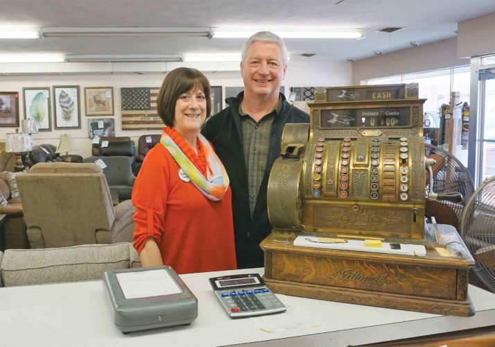 Cathy and Steve Springan stand at the counter of Springan Furniture, where an heirloom cash register holds a prominent place. The cash register remains in use.   Jill Schramm/MDN