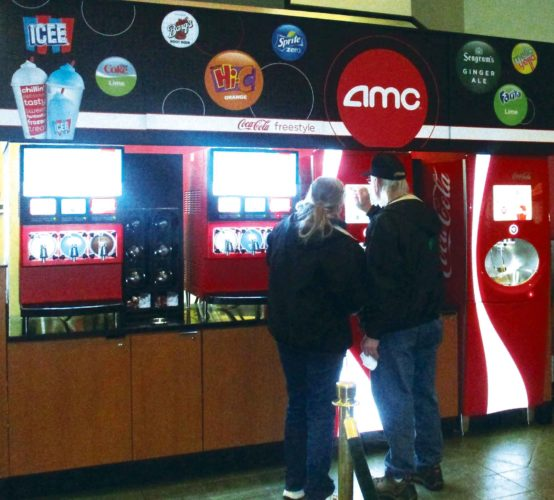 Allan Blanks/MDN  Lori Haagenstad, left, and her husband,  Norman Haagenstad, operate the newly installed pop machine at AMC Dakota Square 9.