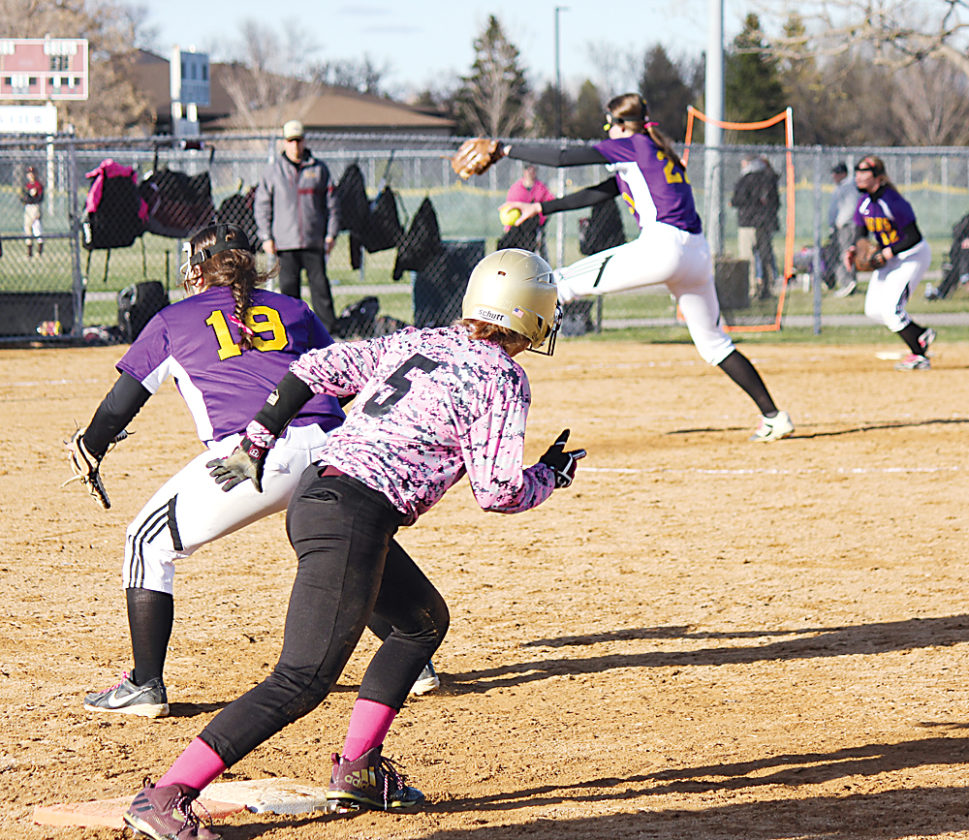 Alex Eisen/MDN Minot High senior Riley Irmen (5) gets a lead off from first base guarded by Bishop Ryan's Hannah Candrian (19) while Annika Stewart pitches Thursday evening in the second game of a doubleheader held at the South Hill Softball Complex.