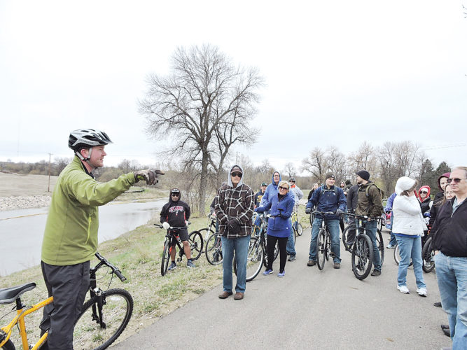 "Kim Fundingsland/MDN Ryan Ackerman, left, Ackerman-Estvold Engineering, explains how future improvements to recreation paths will be incorporated into Minot's flood protection plan in the area of the Wee Links and the Water Treatment Plant. The stop was one of several held during Saturday's ""Ride the River"" hosted by the Friends of the Souris River."