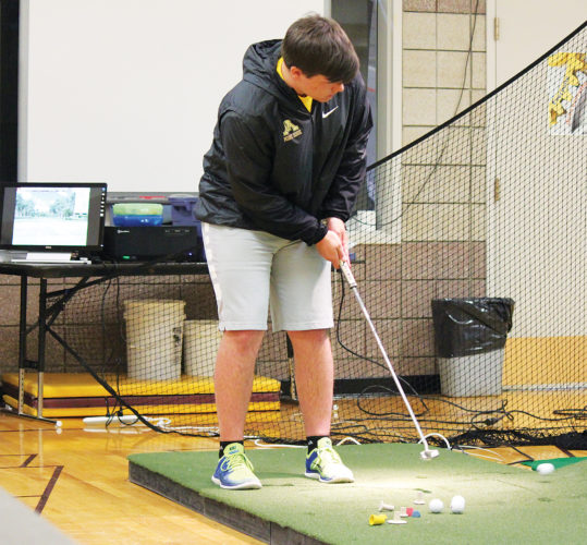 Alex Eisen/MDN Minot High junior Spencer Ross putts toward the golf simulator Monday during an indoor practice held at the Minot High Central Campus.