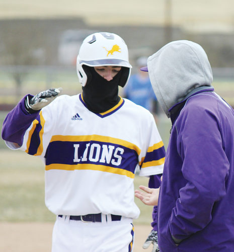 Alex Eisen/MDN Bishop Ryan sophomore Luke Voorhies exchanges a high-five with first base coach Ben Magnuson after getting a single in the first game of a doubleheader against Max-Garrison-White Shield on Tuesday at Jack Hoeven Field.