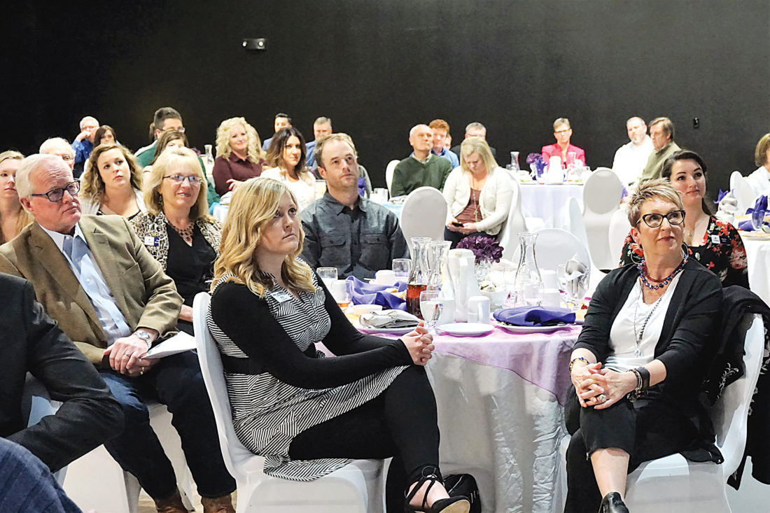 Jill Schramm/MDN Megan Laudenschlager and Pam Karpenko, foreground, and some other Visit Minot board members and staff and community members listen to a guest speaker at the Visit Minot annual meeting in the Sleep Inn & Suites Thursday.