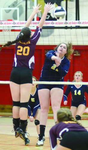 Morning Journal/Patti Schaeffer United's Taylor Miller spikes the ball against South Range's Cara Mason (20) on Wednesday. Looking on are United's Kylie Daggy and Rachel Bowen.