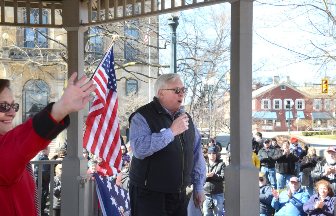 Morning Journal/Patti Schaeffer Columbiana County Republican Party Chairman Dave Johnson welcomes one and all to a rally for President Donald J. Trump at the gazebo in Lisbon. Johnson served as the emcee for the event, which celebrated Trump's presidency, with GOP favorites like Anita Frazer, shown waving at the left, who helped organize Saturday's event.