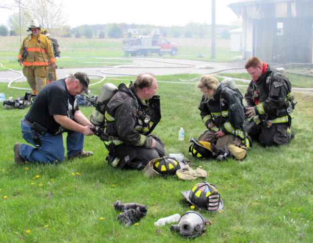Morning Journal/Larry Shields  After battling the fire and heavy smoke at the residence at 4157 Lisbon Road near Franklin Square, Leetonia firefighters change airpack bottles and show the strain. From left, Ron Hall Jr., assists Capt. Randy Hall while firefighter/EMT Jordan Rhoads is assisted by firefighter Jesse Bell in changing airpacks.