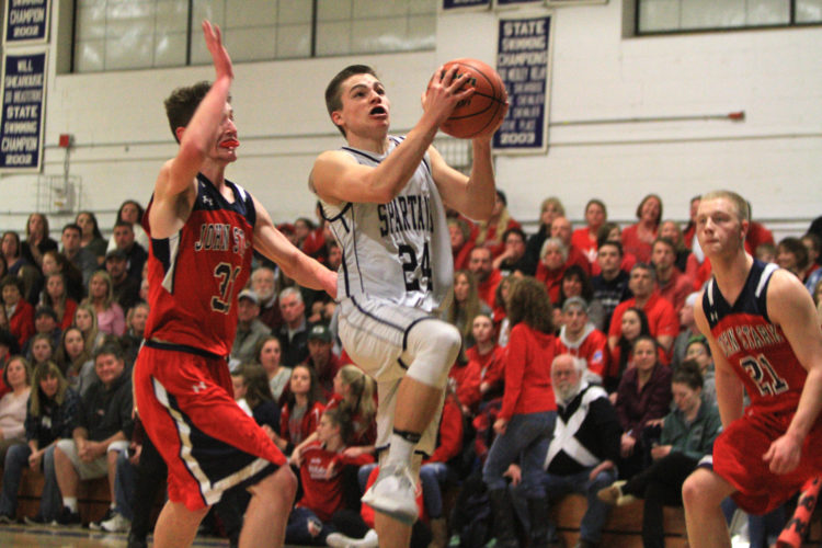 Staff photo by Jason Orfao Milford senior Weston Pare elevates to the hoop past John Stark senior Cooper Gorski (31) on Saturday night during the Spartans' 60-41 quarterfinal victory at Milford.