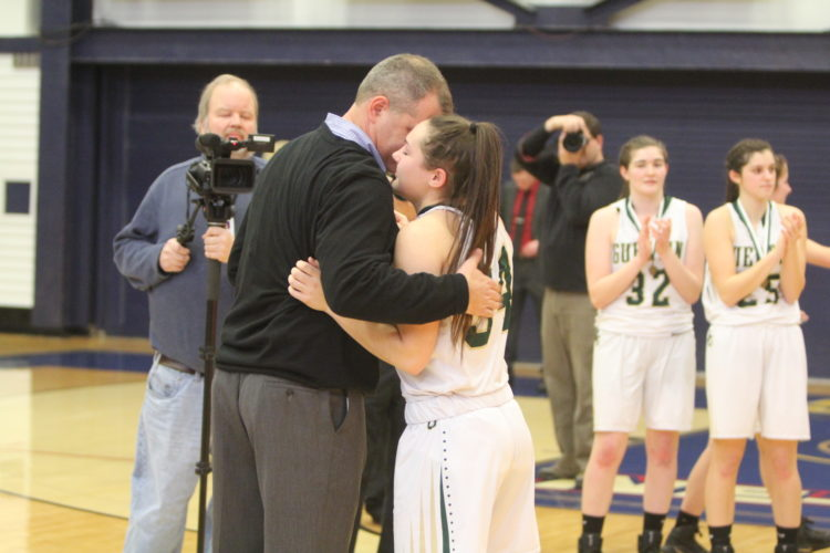 Staff photo by TOM KING Bishop Guertin's Meghan Cramb gets a hug from her coach, Brad Kreick, while getting her medal after Saturday's title game win over Bedford.