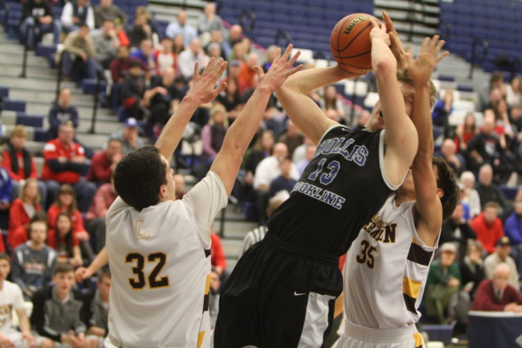 Staff photo by TOM KING Hollis Brokline's Matt Simco tries to force up a shot against the defense of Lebanon's Chris Nulty (32) and Noah Didehbani (35) during Wednesday night's Divison II semifinal at UNH.