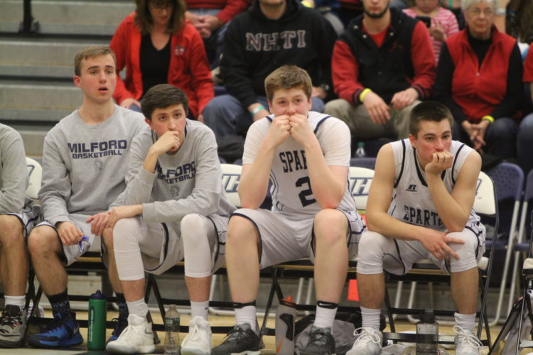 Staff photo by TOM KING/Milford's Evan Ryan (20) and the rest of the Spartans' bench wear a dejected look in the final moments of Coe-Brown's 63-52 Division II semifinal win on Wednesday at UNH.