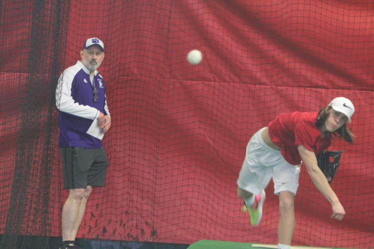 Staff photo by TOM KING Nashua South sophomore pitcher Chase Hart throws while under the watchful eye of Panthers pitching coach Jim Harvell during tryouts at an indoor facility near the school as tryouts began Monday for spring sports.