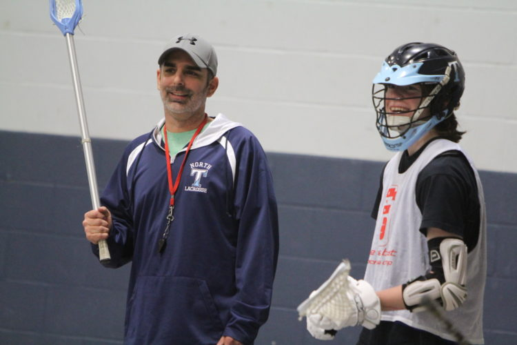 Staff photo by TOM KING New Nashua North boys lacrosse coach Rod Martin shares a laugh with Titans senior Brandon Martin during practice the other night.