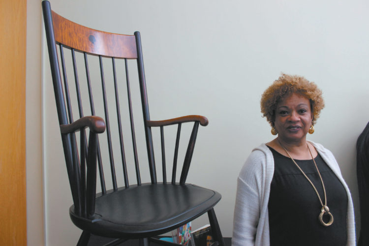 Photo by KATHY CLEVELAND JerriAnne Boggis, founder of the Harriet Wilson Project, is shown with the Harriet E. Wilson Memorial Chair. The chair was dedicated March 15 in Milford's Wadleigh Memorial Library.