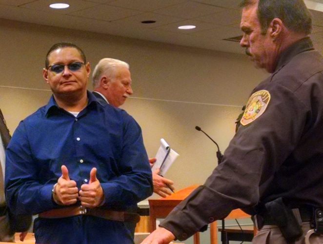 Staff file photo by Dean Shalhoup Ernesto Rivera gives a thumbs-up as he leaves a 2015 court hearing around the time he was convicted of charges that sent him to prison for 30-plus years.