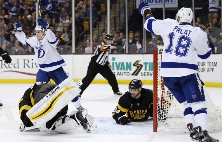 Tampa Bay Lightning's Brayden Point, top left, and Ondrej Palat (18), of the Czech Republic, celebrate a the goal by Nikita Kucherov as Boston Bruins' Adam McQuaid (54) and Tuukka Rask lie on the ice during the third period of an NHL hockey game in Boston on Thursday. The Lightning won 6-3. (AP Photo/Michael Dwyer)