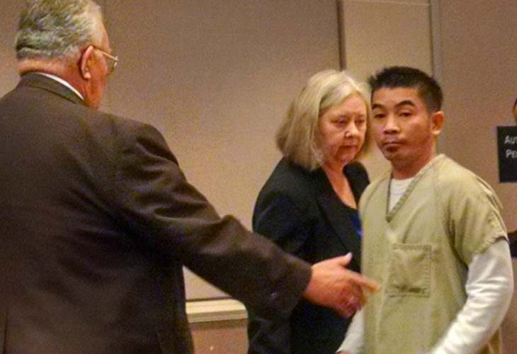 Staff file photo by Dean Shalhoup Nghia Huynh glances toward the visitor seats as a court officer prepares to escort him from court  following his sentencing hearing in December 2015. Huynh will be eligible for parole in August.