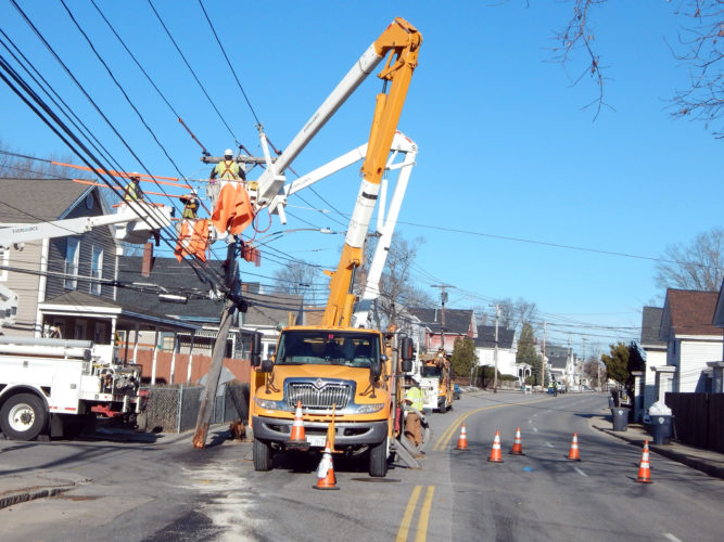 Staff photo by Dean Shalhoup Eversource crews work to stabilize power lines ahead of replacing the utility pole at left, which was snapped by a vehicle around 4 a.m. Thursday at Amherst and Fairmount streets.