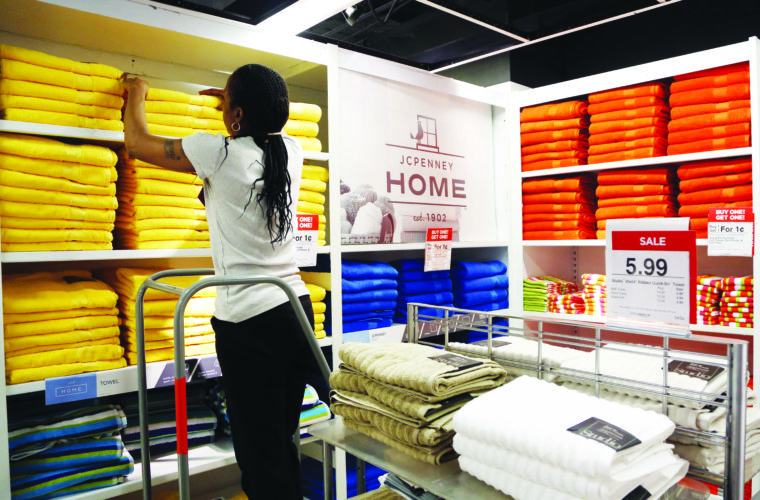 "FILE - In this  March 10, 2016 file photo, a sales clerk arranges towels that are part of a ""Buy One Get One for a Penny"" sale at a J.C. Penney store, in New York. The last two months saw the largest decline in retail jobs since December 2009, when the economy was coming out of deep funk. But the combined 60,600 job losses have less to do about the economy and more to do with shoppers' dramatic shift in spending online.   (AP Photo/Mark Lennihan)"