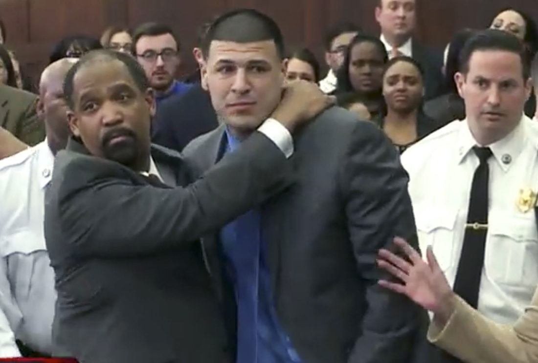 In this still image from video, Aaron Hernandez, center, is hugged by defense attorney Ronald Sullivan Friday, April 14, 2017, in court in Boston, after being found not guilty of murder in the 2012 shootings of two men in a drive-by shooting in Boston. (WHDH-TV via AP, Pool)