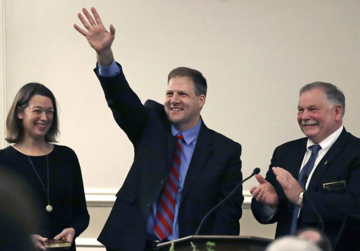 FILE - In this Jan. 5, 2017 file photo, New Hampshire Gov. Chris Sununu waves as he stands with his wife Valerie, left, and Speaker of the House Shawn Jasper after taking the oath of office at the State House in Concord, N.H. Sununu set an ambitious agenda for a first-term governor, and as he marks his first 100 days in office, he's made headway on some while seeing little to no progress -- or outright losses -- on others. (AP Photo/Charles Krupa, File)