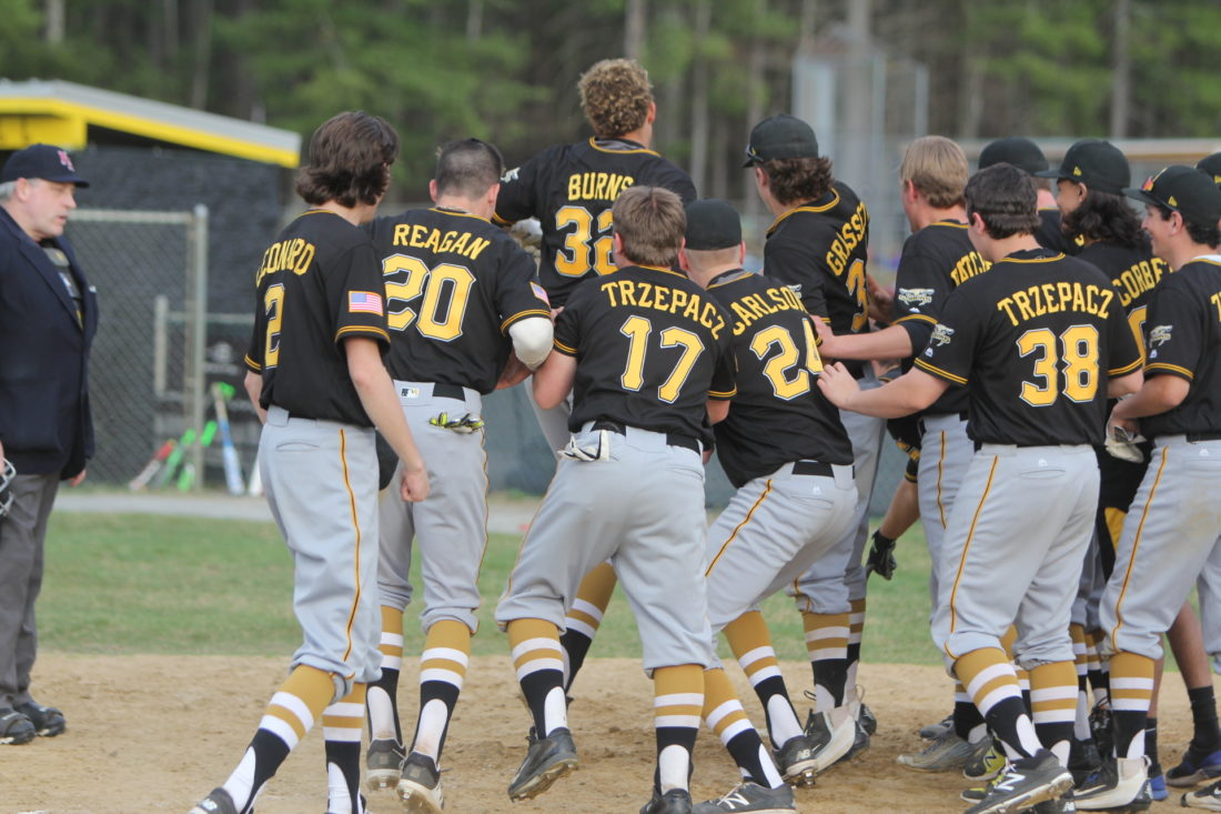 Staff photo by TOM KING Souhegan's Alec Burns gets mobbed by his teammates at home plate after hitting a walkoff homer to give the Sabers a 7-6 win over Hollis Brookline on Monday.