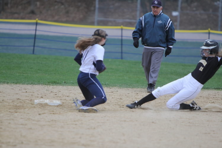 Staff photo by TOM KING Souhegan's Rheanna Wilson slides safely into second as Milford infielder Jenna De Angelis looks out to where the ball got away, one of the few Spartan blemishes in a 4-1 Milford win on Wednesday.