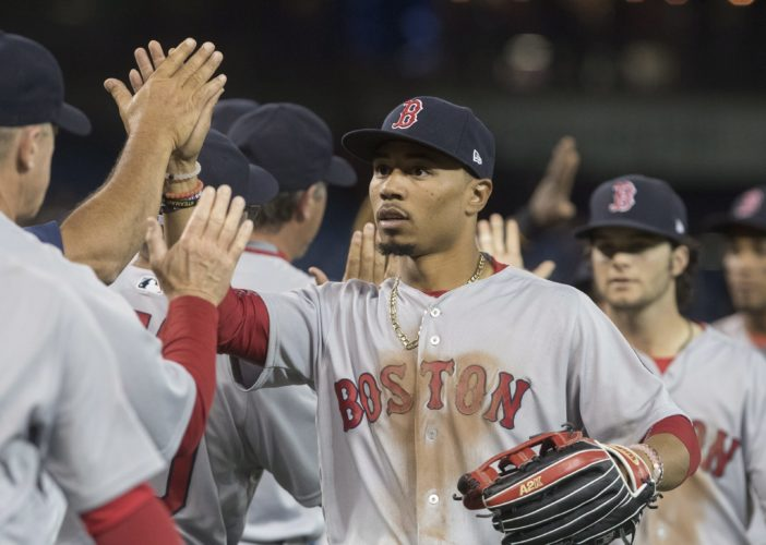 Boston Red Sox's Mookie Betts gets high-fives from teammates after they defeated the Toronto Blue Jays 4-1 in 10 innings of a baseball game in Toronto on Thursday, April 20, 2017. (Fred Thornhill/The Canadian Press via AP)